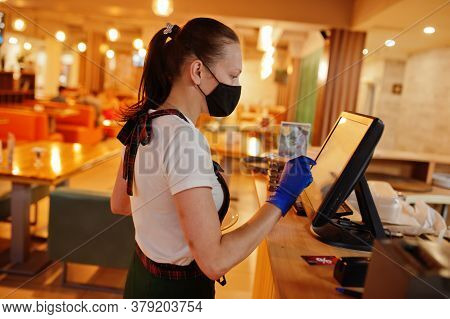 Waiter In Protective Mask In The Restaurant At Counter With Cashbox Working At Bar.