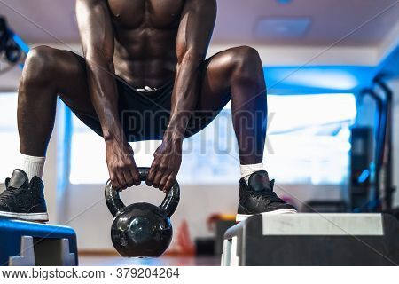 Young African Man Training Inside Gym - Fit Male Doing Kettlebell Exercise Workout Session In Sport