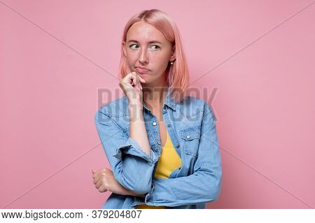 Pensive Young Woman With Dyed Pink Hair Looking Aside