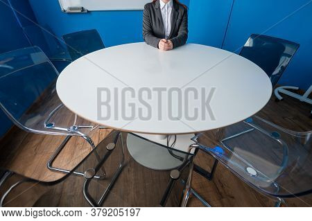 A Faceless Business Woman In A Suit Sits Alone At A Round Table In A Meeting Room. The Female Boss I