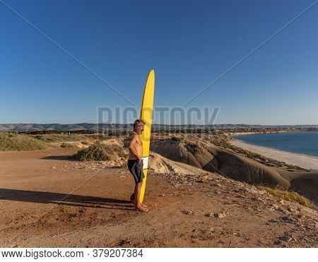 Portrait Of Mature Senior Surfer Looking At The Ocean With Vintage Surfboard On An Empty Beach