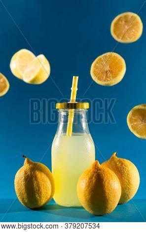 Glass Bottle With Lemon Slush Soda Inside, A Yellow Straw And 3 Whole Lemons At The Base. Several Ha