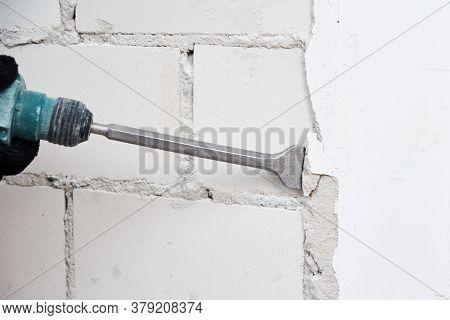 Renovation Concept. Man With Demolition Hammer Remove Stucco From Wall