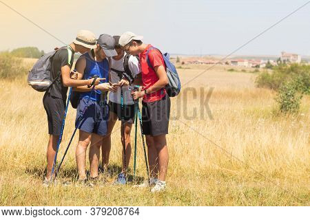 Young People With Trekking Poles Doing The Way Of Saint James In Spain Seeing On Their Mobile Phone