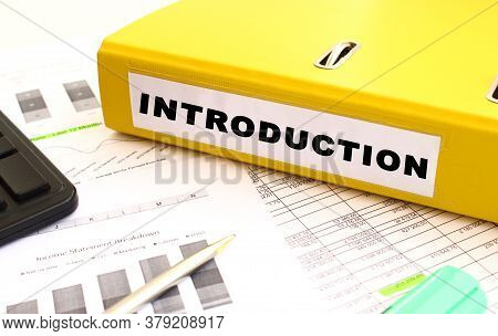The Yellow Document Folder Is On The Office Desk. Nearby A Calculator And Finance Graphs. Inscriptio