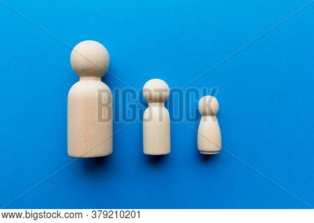 Single Parent Concept - Male And Female Wooden Figures Showing A Male Adult And Male And Female Chil