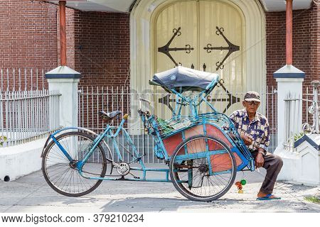 Semarang, Indonesia - October, 31, 2017: Taxi Driver Waiting For Customers In Front Of A Church, In
