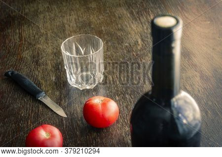Sealed Bottle Of Red Wine On Wooden Table With Ripe Tomatoes. Full Bottle Of Wine With Cork, Two Red