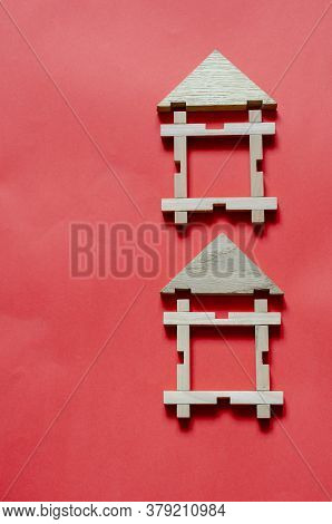 Two Wooden Houses From A Childrens Constructor On A Coral Background. Simple Houses From Wooden Geom