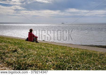 Harlingen, Netherlands, July, 23, 2020:silhouette Back Of Young Woman On A Dike Overlooking The Wadd