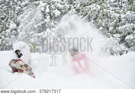 Young Couple Skiers In Ski Suits And Helmets Throwing Fresh Powder Snow In The Air And Smiling. Man