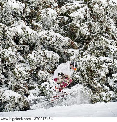 Skier In White Jacket And Helmet Doing Tricks In The Mountains In Winter Season, Jumping On Slope Me