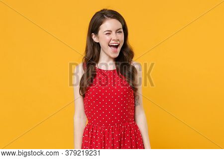Cheerful Funny Young Brunette Woman Girl In Red Summer Dress Posing Isolated On Yellow Wall Backgrou