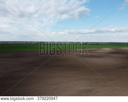 Picturesque Farmland, Aerial View. Beautiful Sky Over A Plowed Field.