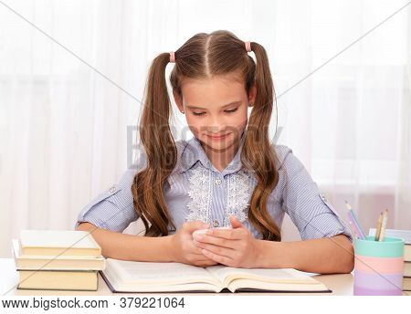 Education And School Concept. Child Is Sitting At The Desk And Using Mobile Phone. Smiling Cute Litt