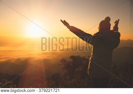 Copy Space Of Silhouette Woman Raise Hand Up On Top Of Mountain And Sunset  Background. Freedom Feel