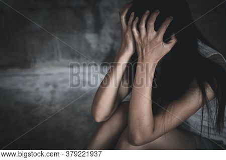 Young  Women Sitting In Dark Room Feeling Pain With Life Problem.  Suffering From Husband Violence,