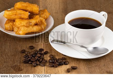 Normal Breakfast With Deep-fried Dough Stick In A White Ceramic Plate, Pile Of Coffee Beans Hot Blac