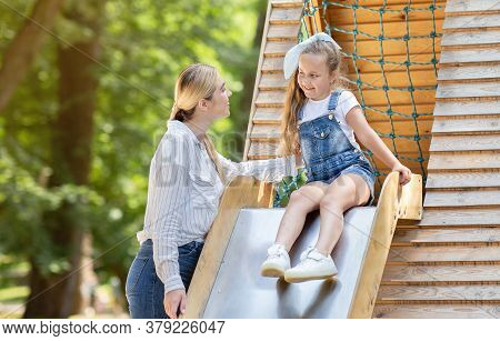 Babysitting. Little Kid Girl Riding The Slide Playing With Babysitter Woman On Playground Outdoor.