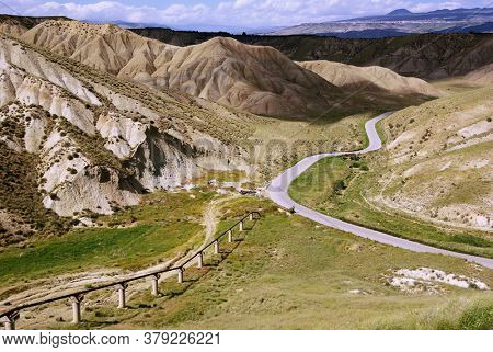 dramatic landscape of Sicily rural road crosses eroded rock formation