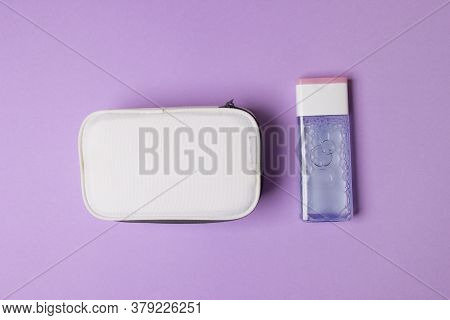 White Make-up Box And Bottle With Tonic On Purple Colored Paper Background.