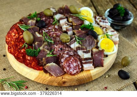 Wooden Cutting Board With Prosciutto, Bacon, Sausages, Boiled Eggs And Olives On Old Table. Selectiv