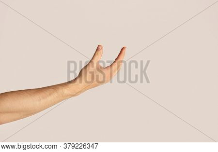 Unrecognizable Young Guy Presenting Something On Light Background, Closeup. Mockup For Your Design