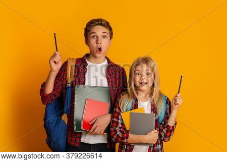 Great Idea Concept. Excited Siblings Brother And Little Sister Raising Hands With Pencils Up Over Ye