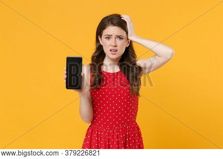 Worried Young Brunette Woman Girl In Red Summer Dress Posing Isolated On Yellow Background. People L