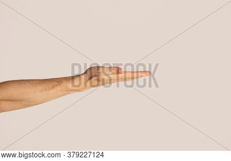 Millennial Man Displaying Something Against Light Background, Close Up. Empty Space For Design