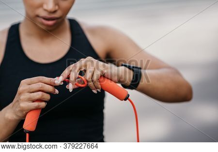 Adjustment Of Sports Equipment. Serious African American Girl In Sportswear With Fitness Tracker Adj