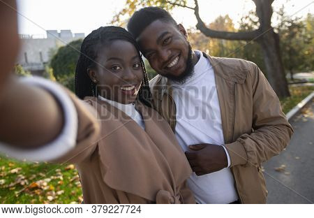 Selfie Time. Cheerful Black Girl Taking Self-portrait With Her Boyfriend While Walking In Park, Clos