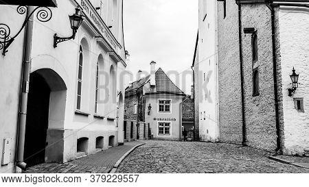 Tallinn, Estonia - May 26, 2019: Man Walking Down The Street In Old Town In Tallinn, Black And White
