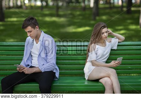 Young Girl And Her Boyfriend With Cellphones Ignoring Each Other During Dull Date At Park