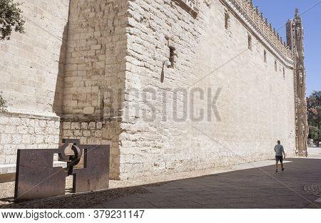 Valladolid, Spain - July 18th, 2020: Visitor Walking Near Modern Art Sculpture Beside Colegio De San