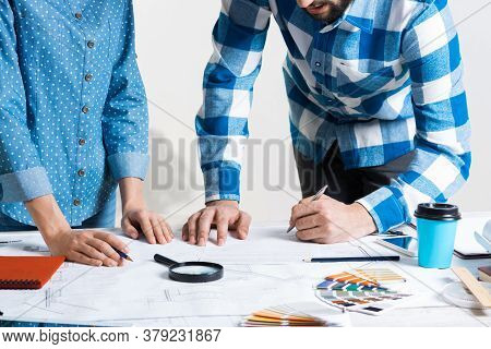 Man Writing With Pen On Technical Drawing. Creative Team Of Designers Together Working With Construc