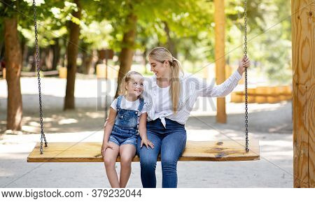Mother And Little Daughter Swinging On Swings Together Having Fun On Outdoor Playground In Park. Hap