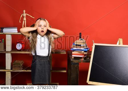 Schoolgirl With Frightened Face In Classroom. Kid And School Supplies