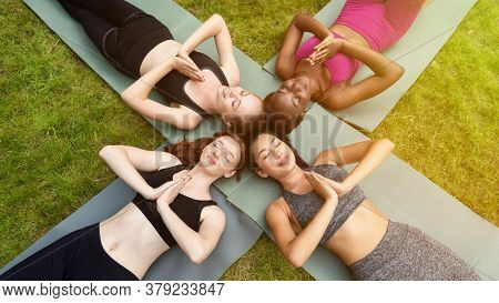 Yoga Meditation. Overhead View Of Multinational Women Lying On Sports Mats And Gesturing Namaste, Ou