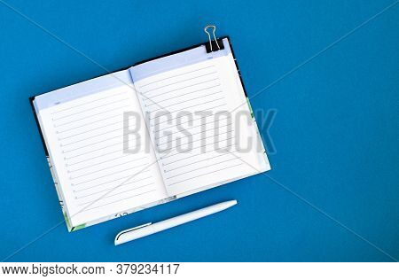Top View Of A Notepad And Pen On A Blue Background. School Notebook For Notes. Copy Space. Mortgage