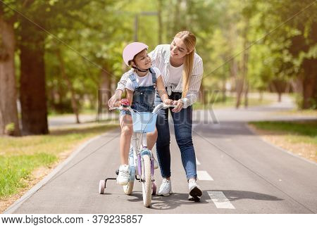 Mom Teaching Little Daughter To Ride Bicycle With Stabilisers Encouraging Her Outdoors. Weekend Conc