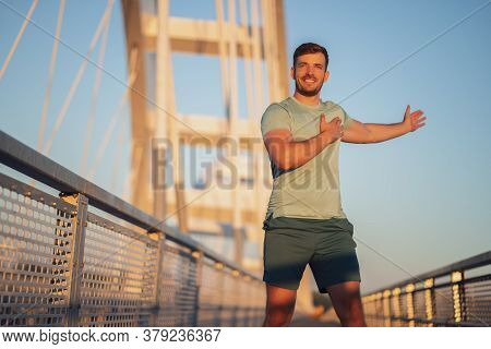 Young Man Is Exercising Outdoor On Bridge In The City.