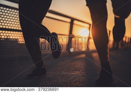 Body Part Silhouettes Of Couple Who Is Jogging In The City In Sunset.
