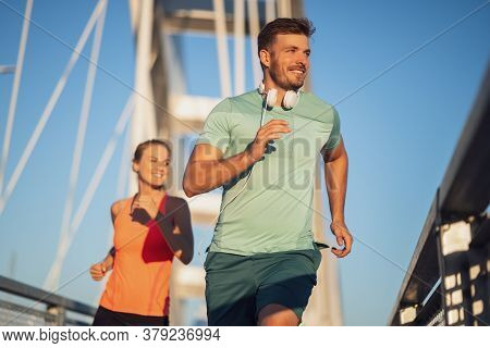 Young Couple Is Exercising Outdoor On Bridge In The City.