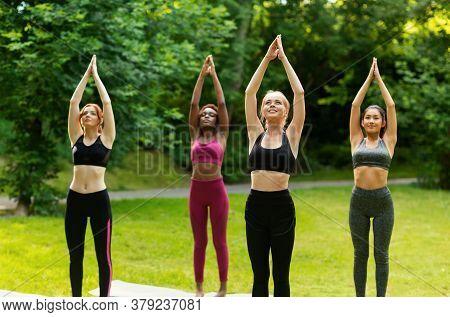 Beautiful Multinational Girls Doing Sun Salutations Yoga Flow At Green Park