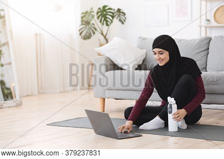 Online Fitness Tutorials. Sporty Muslim Woman Preparing For Home Workout, Using Laptop While Sitting