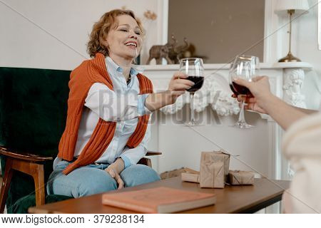 Old Friends Met In Stylish Living Room And Drinking Wine. Happy Smiling Senior Blonde Woman Giving A