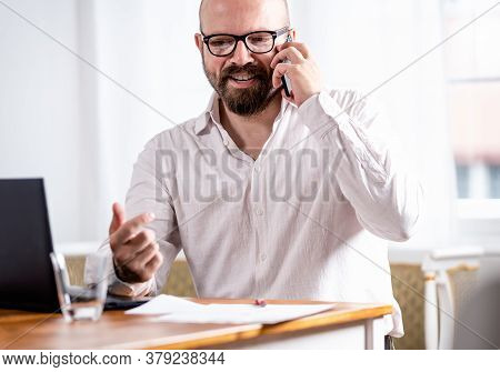 Man Speaking On Cell Phone. Bearded Man Speaking On Cell Phone And Reading Book. Happy Young Busines