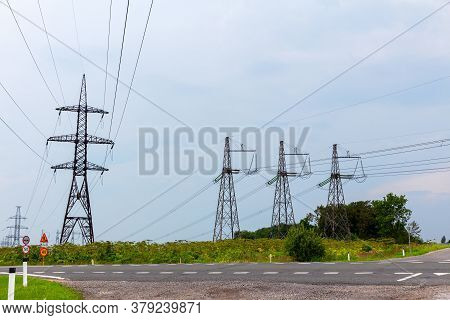 High Voltage Power Line Masts And Highways In Rural Areas