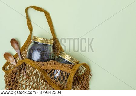 A Reusable String Bag Contains Two Wooden Spoons And Two Glass Jars Of Tea On A Mint Background. Reu